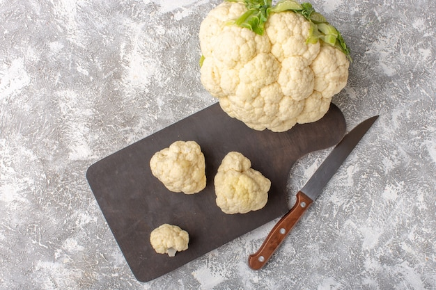 Top view of fresh cauliflower with knife and on the light-white surface