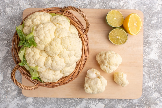 Top view of fresh cauliflower with lemon on white-light surface