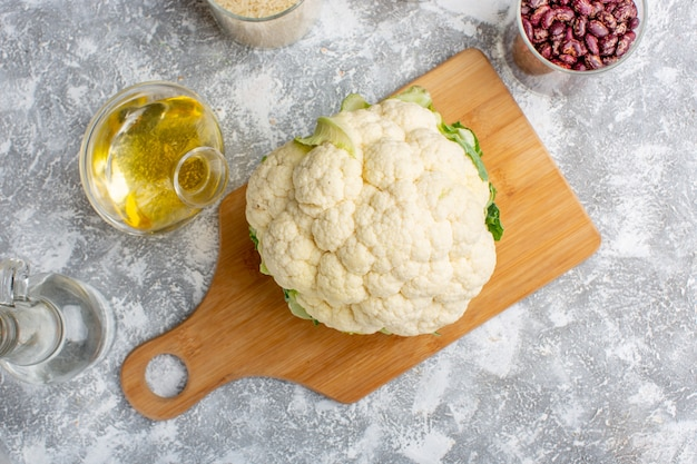 Top view of fresh cauliflower with oil and beans on grey-white surface