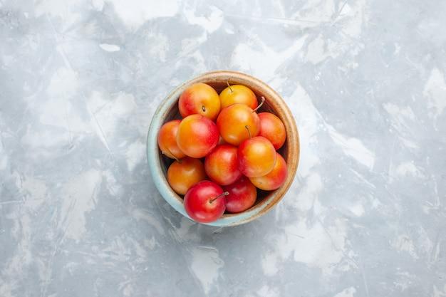 Vista dall'alto ciliegie-prugne fresche aspro e fresco all'interno della pentola sulla scrivania leggera frutta acida fresca pastosa