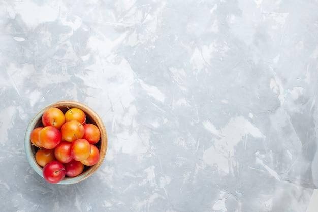 Vista dall'alto ciliegie-prugne fresche aspro e fresco all'interno pentola sulla scrivania bianca frutta acida fresca pastosa