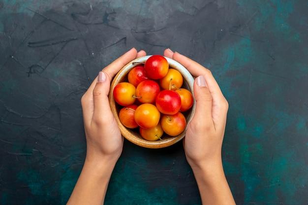 Vista dall'alto ciliegie-prugne fresche frutta acida e pastosa all'interno di una piccola pentola sulla superficie blu scuro frutta fresca dolce