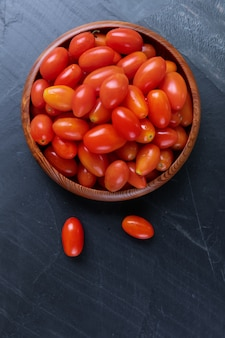 Top view of fresh cherry tomatoes on bowl wooden with white wall.