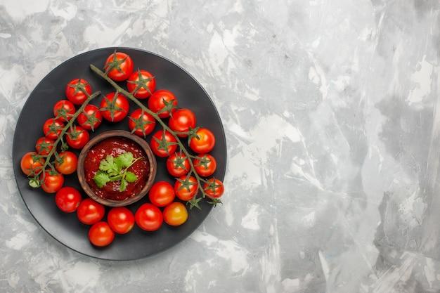 Pomodori ciliegia freschi vista dall'alto all'interno del piatto sulla superficie bianca