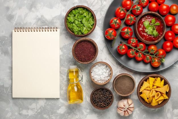 흰색 표면에 다른 조미료와 기름으로 접시 안에 상위 뷰 신선한 체리 토마토
