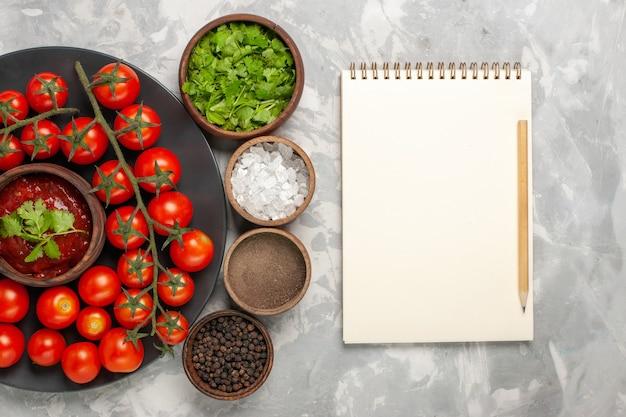 白い表面にさまざまな調味料を入れたプレート内の新鮮なチェリートマトの上面図