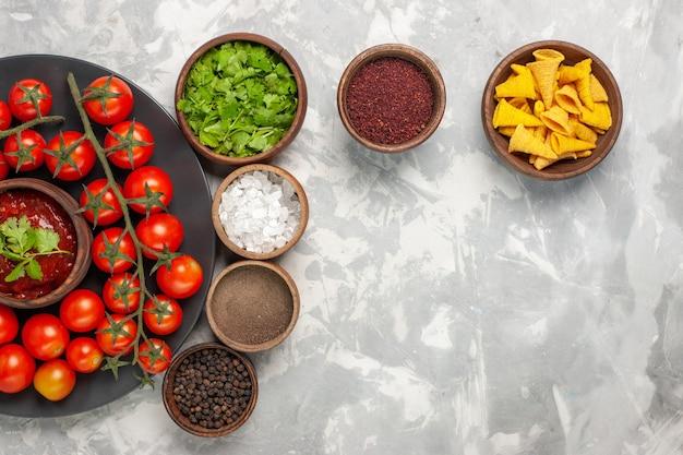 白い机の上にさまざまな調味料とプレート内の新鮮なチェリートマトの上面図