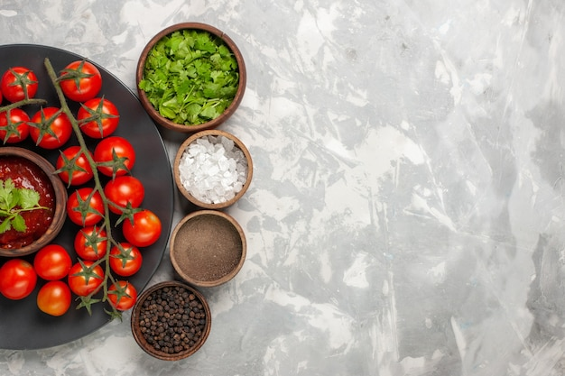 Вид сверху свежих помидоров черри внутри тарелки с разными приправами на белой поверхности