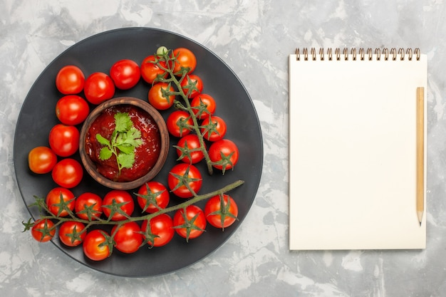 Top view fresh cherry tomatoes inside plate with notepad on the white surface