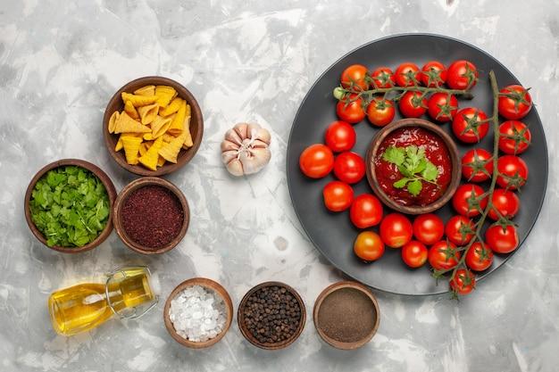 Vista dall'alto pomodorini freschi all'interno del piatto con condimenti sulla superficie bianca