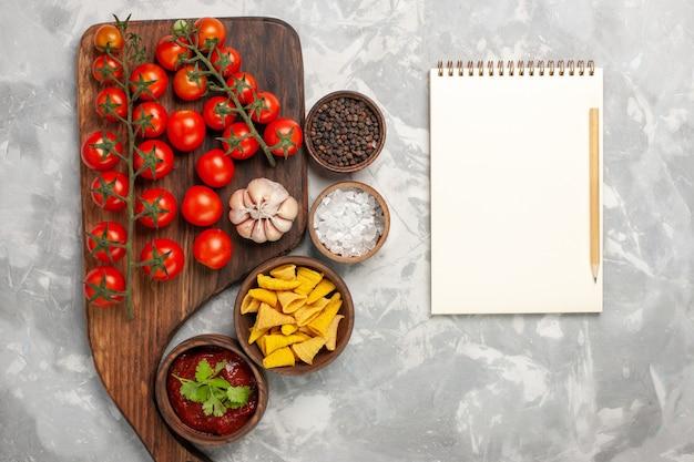 Vista dall'alto pomodorini freschi con diversi condimenti e blocco note sulla superficie bianca