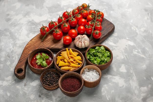白い机の上にさまざまな調味料と新鮮なチェリートマトの上面図