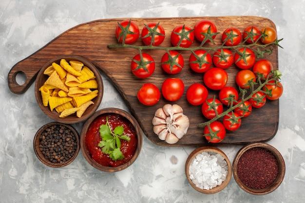 흰색 표면에 다른 조미료와 상위 뷰 신선한 체리 토마토