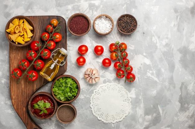 Vista dall'alto pomodorini freschi con condimenti e verdure sulla scrivania bianca