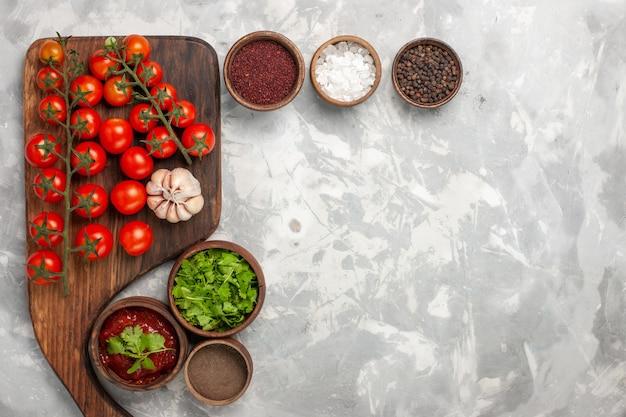 Vista dall'alto pomodorini freschi con condimenti e verdure su superficie bianca