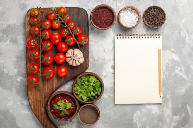 흰색 표면에 조미료 메모장 및 채소와 상위 뷰 신선한 체리 토마토