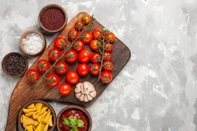 흰색 책상에 조미료와 상위 뷰 신선한 체리 토마토