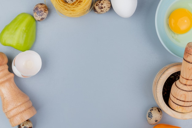 Top view of fresh chicken egg yolk and white on a blue bowl with cracked egg shells with salt shaker on a white background with copy space