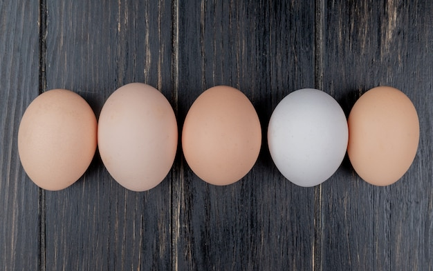 Top view of fresh chicken eggs arranged in a line on a wooden background