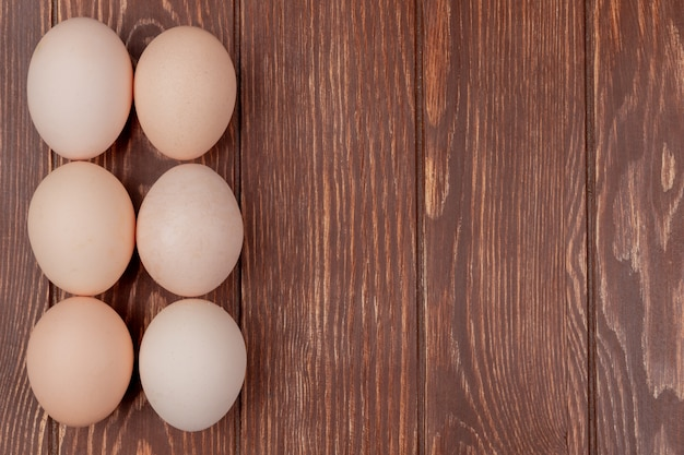 Top view of fresh chicken eggs arranged on a wooden background with copy space