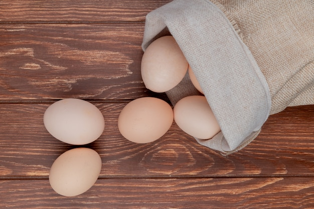 Top view of fresh chicken eggs on a burlap bag on a wooden background