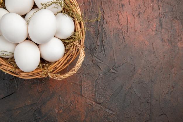 Vista dall'alto uova di gallina fresche all'interno del cesto sul tavolo scuro cibo animale vita sana foto a colori fattoria spazio libero per il testo