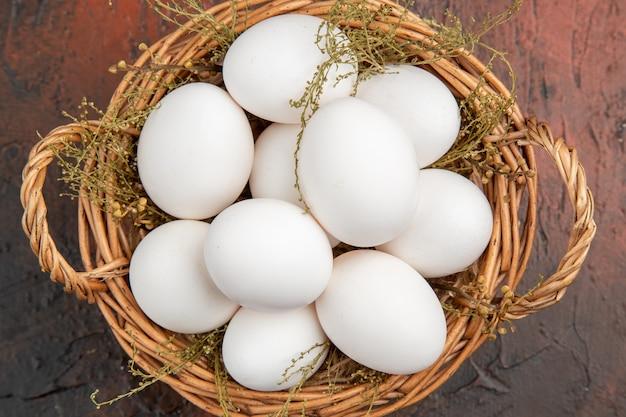 Vista dall'alto uova di gallina fresche all'interno del cesto su un tavolo scuro