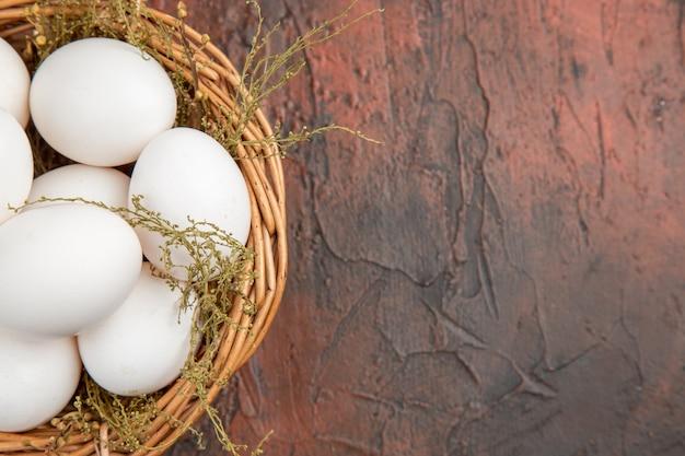Vista dall'alto uova di gallina fresche all'interno del cesto sul tavolo scuro