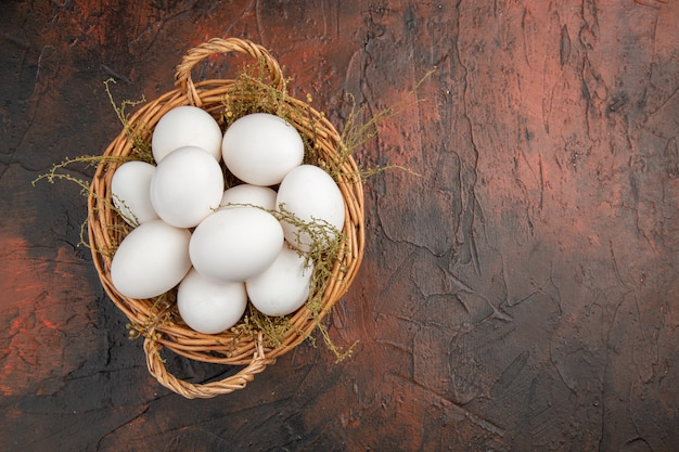 暗いテーブルのバスケットの中の新鮮な鶏卵の上面図