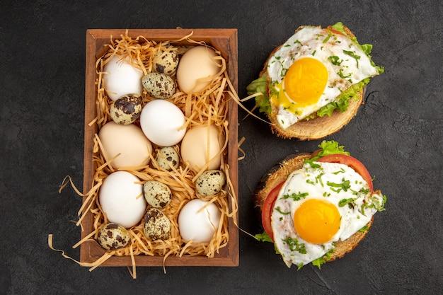 어두운 배경에 달걀 샌드위치가 있는 상자 안에 있는 신선한 닭고기 달걀 사진 음식 식사 아침 식사 동물 색상 아침 차