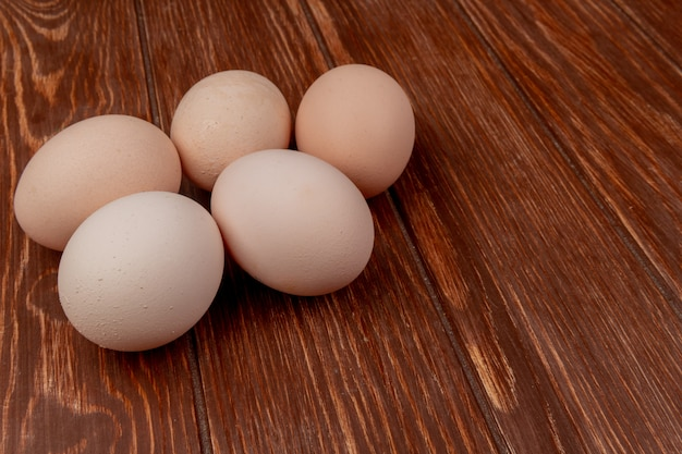 Top view of fresh chicken eggs isolated on a wooden background