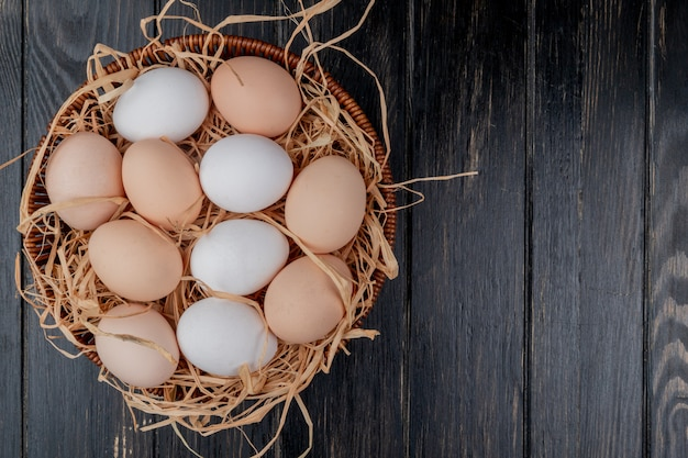 Top view of fresh chicken eggs on nest on a wooden background with copy space