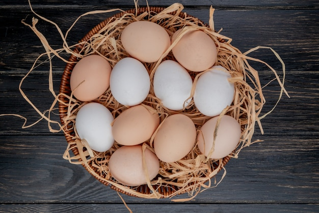 Top view of fresh chicken eggs on nest on a wooden background