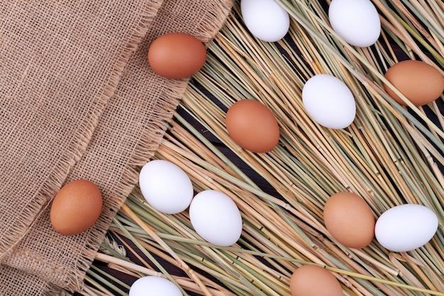 잔디에 상위 뷰 신선한 닭고기 달걀입니다. 밀 짚 잔디와 오래 된 천에 원시 계란의 소박한 구성.