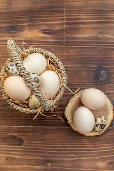Вид сверху свежие куриные яйца с перепелиными яйцами на коричневом деревянном столе еда пирог печь торт выпечка бисквит