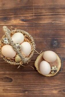 Вид сверху свежие куриные яйца с перепелиными яйцами на коричневом деревянном столе еда пирог печь торт выпечка приготовление печенья