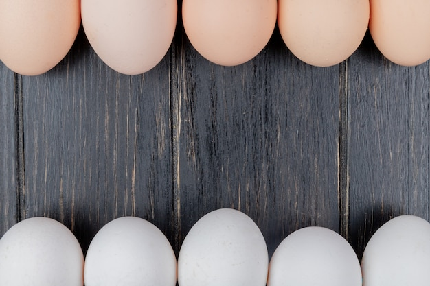 Top view of fresh chicken eggs on a wooden background with copy space