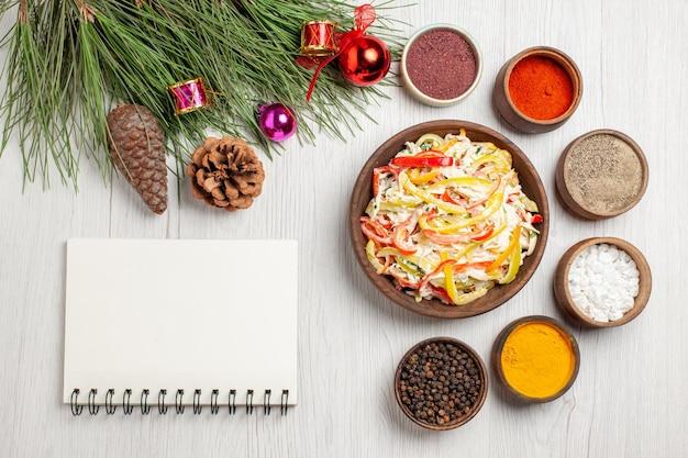 上面図白い机の上のさまざまな調味料の新鮮なチキンサラダスナック熟した食事肉の新鮮なサラダ