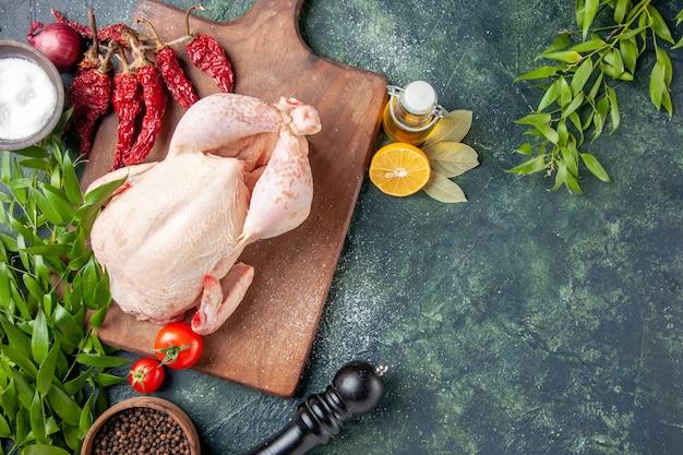진한 파란색 표면에 빨간 토마토가 있는 상위 뷰 신선한 닭고기