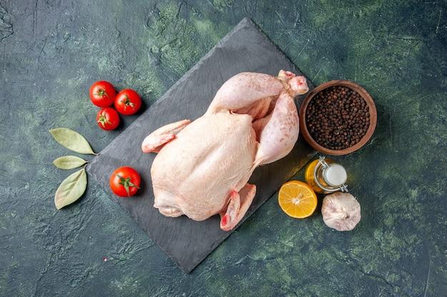 Pollo fresco vista dall'alto con pomodori rossi e pepe su superficie scura