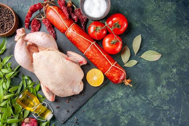 Pollo fresco vista dall'alto con pomodori rossi e salsiccia su superficie scura