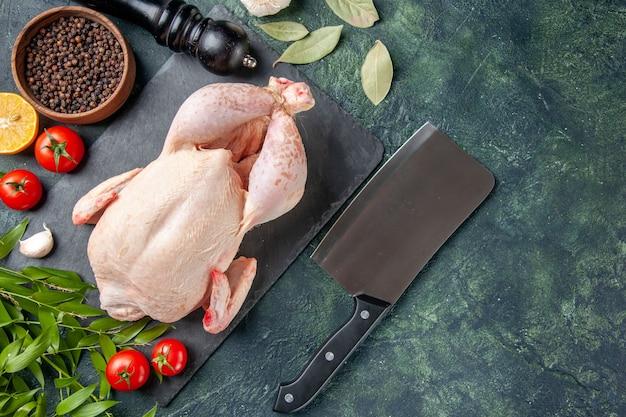 ダークブルーの表面にトマトとコショウを添えた新鮮な鶏肉の上面図