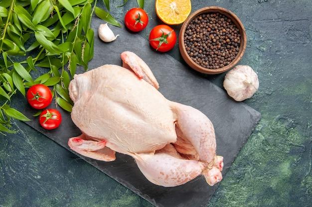 진한 파란색 표면에 토마토와 후추를 넣은 신선한 닭고기