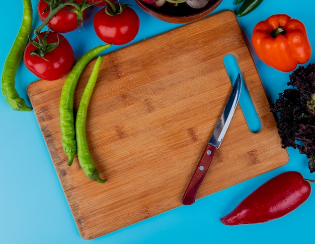 Top view of fresh chili peppers on a wood cutting board with kitchen knife and ripe tomatoes on blue