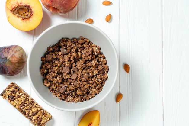 Top view on fresh chocolate granola in grey bowl with figs, peach on white wooden background.