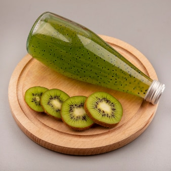 Top view of fresh chopped kiwi slices on a wooden kitchen board with fresh kiwi juice on a glass bottle
