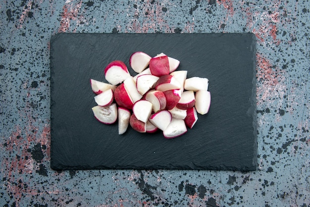 Top view of fresh chopped radishes on dark color cutting board on mixed colors background