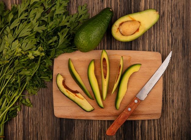 Vista dall'alto di fette fresche tritate di avocado su una tavola da cucina in legno con coltello con prezzemolo isolato su uno sfondo di legno
