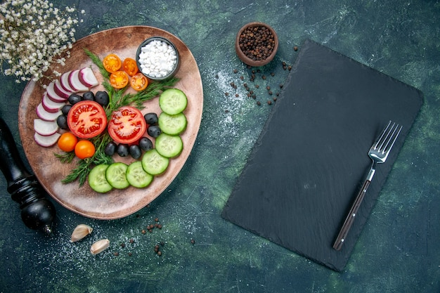 Top view of fresh chopped vegetables olives salt in a brown plate and kitchen hammer garlics fork on wooden cutting board on green black mixed colors background