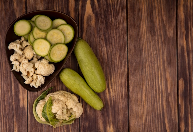 Top view of fresh chopped zucchinis and cauliflower buds on a bowl with whole zucchinis and cauliflower isolated on a wooden background with copy space